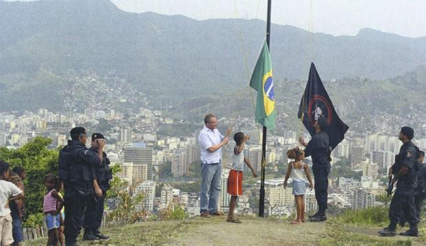 Hasteando a bandeira brasileira e a do Bope no alto do Morro dos Macacos, onde um helicóptero da PM foi abatido em 2009