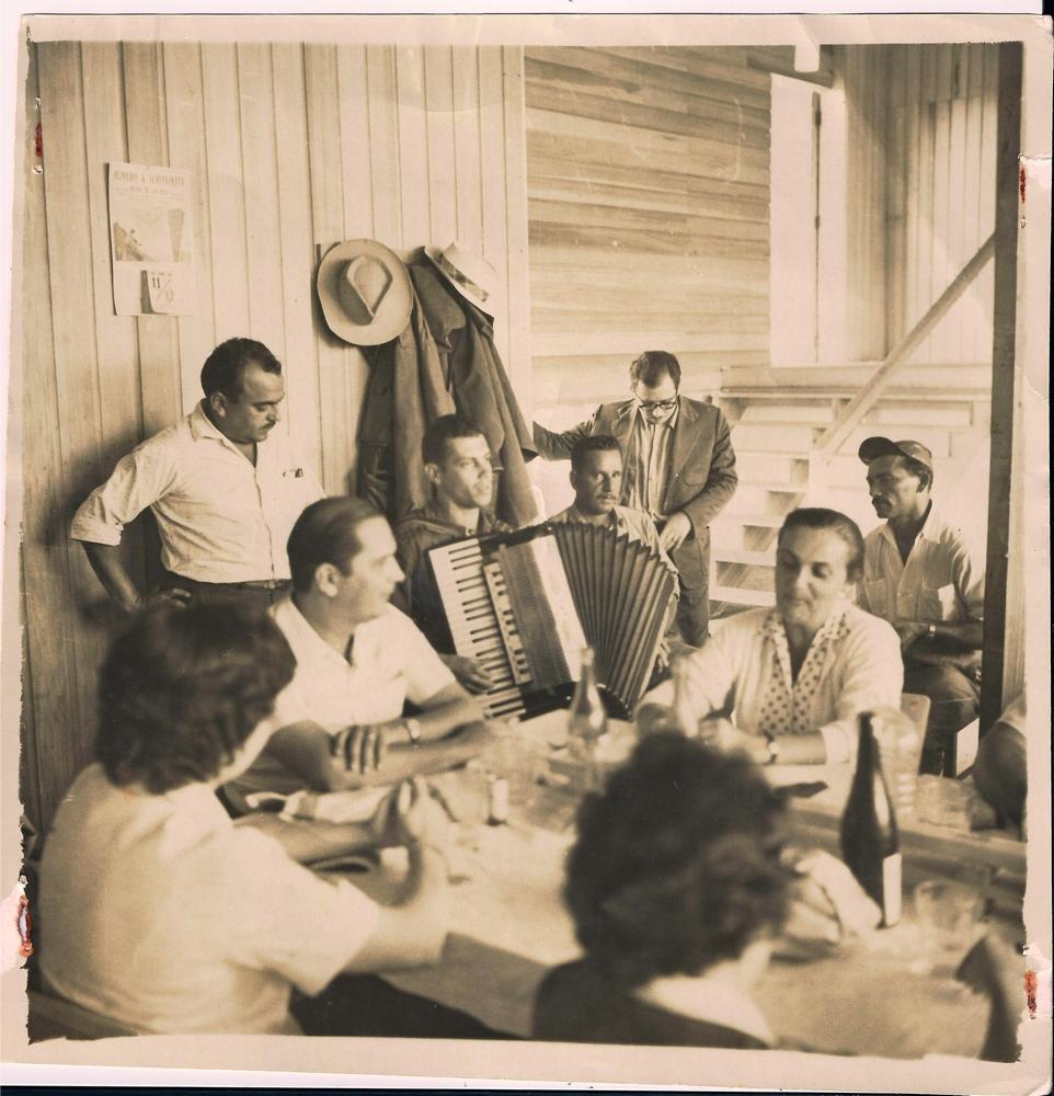 Lelé anima o pessoal com seu acordeão. Na falta de bares e botecos, a turma improvisava música e biritas nos barracões de moradia dos operários que construíam a nova capital federal