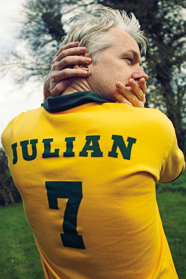 """Quando a Trip pede para Assange ficar de costas e mostrar o nome na camisa, e virar o rosto para trás, o australiano responde: """"Só se eu quebrar meu pescoço"""""""