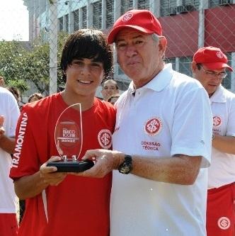Com um dos diretores da base do Inter exibindo um de seus muitos troféus de melhor jogador