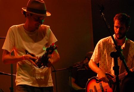 Tatá Aeroplano tocando sua arma de brinquedo ao lado do baixista Renato Cortez