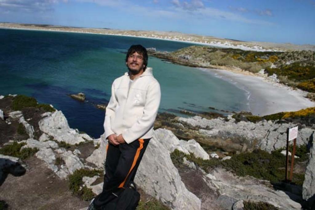 Nosso repórter na praia com o campo minado desativado ao fundo