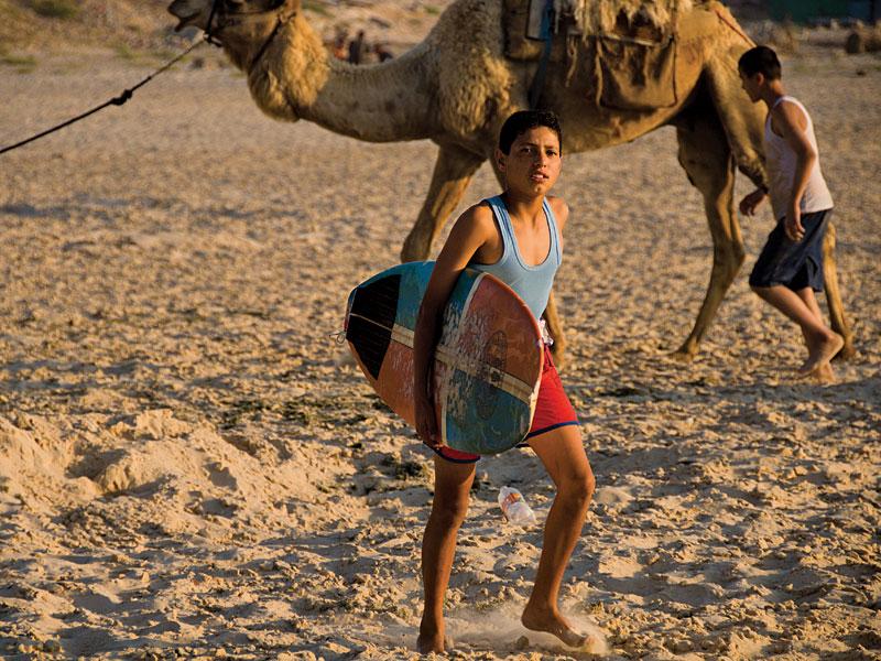 Na praia de Sheik Khazdien, ao norte da Cidade de Gaza, pranchas e camelos disputavam espaço nas areias antes da invasão israelense