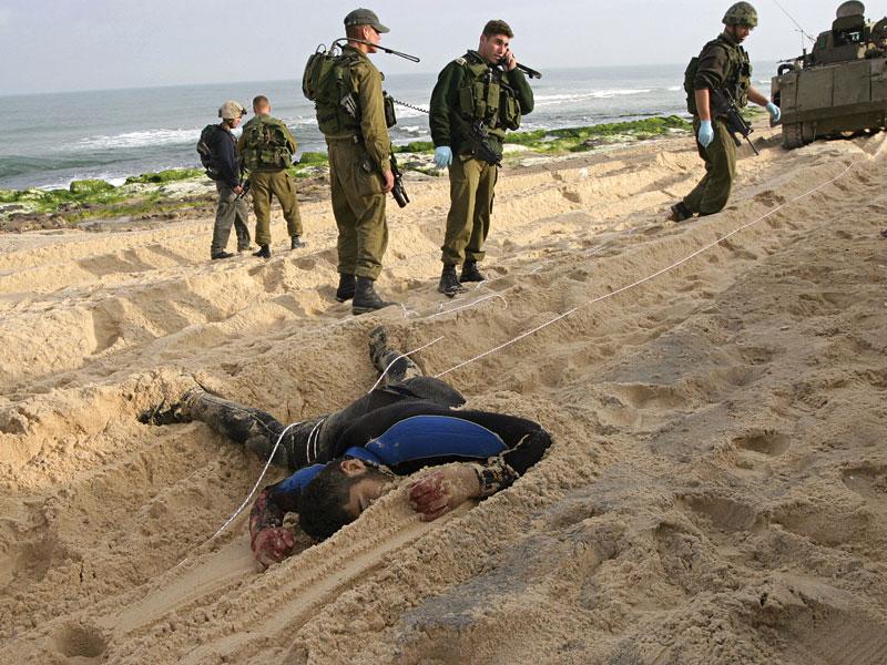 Soldados israelenses e uma de suas vítimas no litoral de Gaza