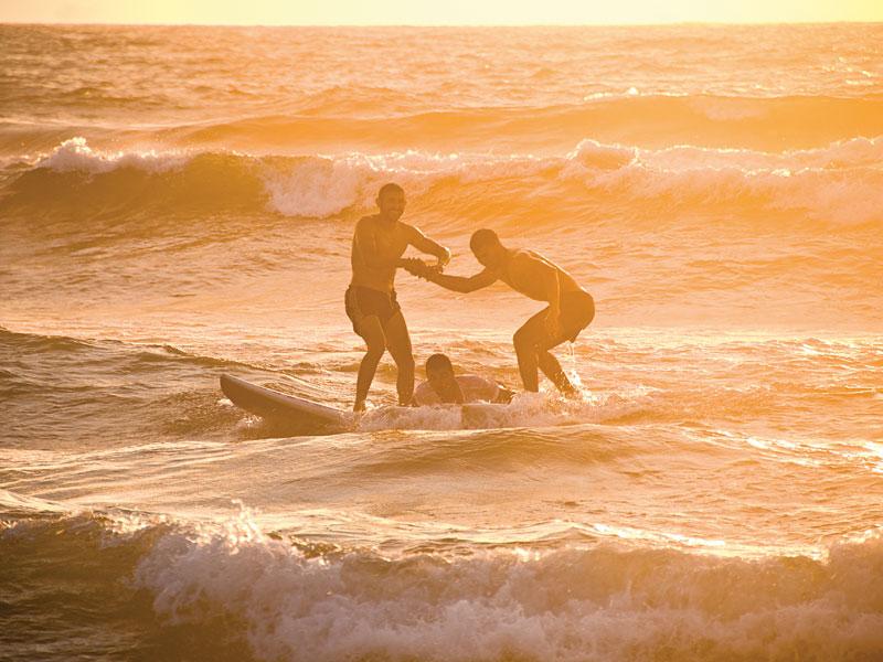 Palestinos dividem a mesma prancha em Gaza, onde o surf não comporta o espírito de competição