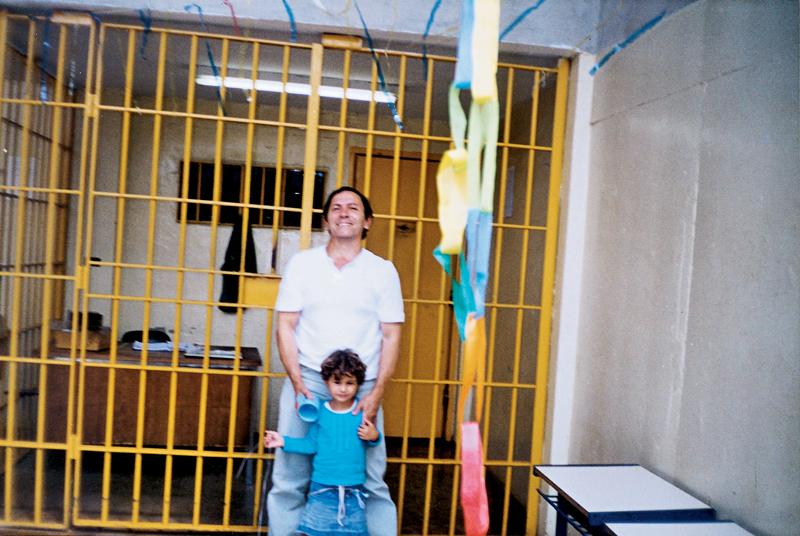 Mendes com a filha de um colega na casa de detenção provisória, em São Paulo, 2002