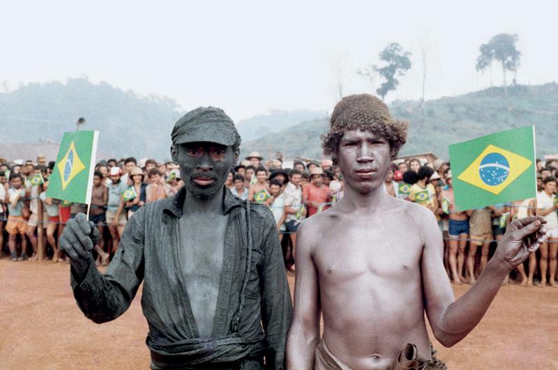 Dois garimpeiros, um coberto da lama de ouro preto, se preparam para a visita de João Figueiredo