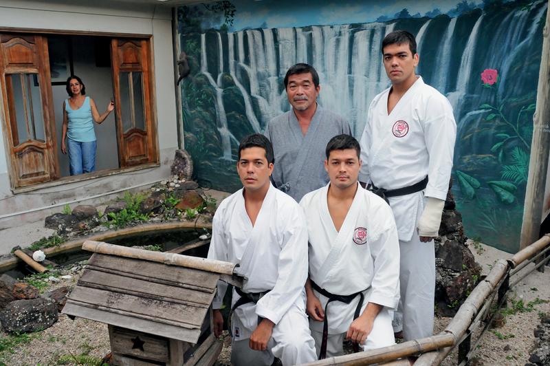 De quimono cinza japonês, Yoshizo cercado pelos filhos, Takeriko, Chinzo e Lyoto, no jardim com lago para carpas. Na janela, a baiana Ana, mãe de Lyoto