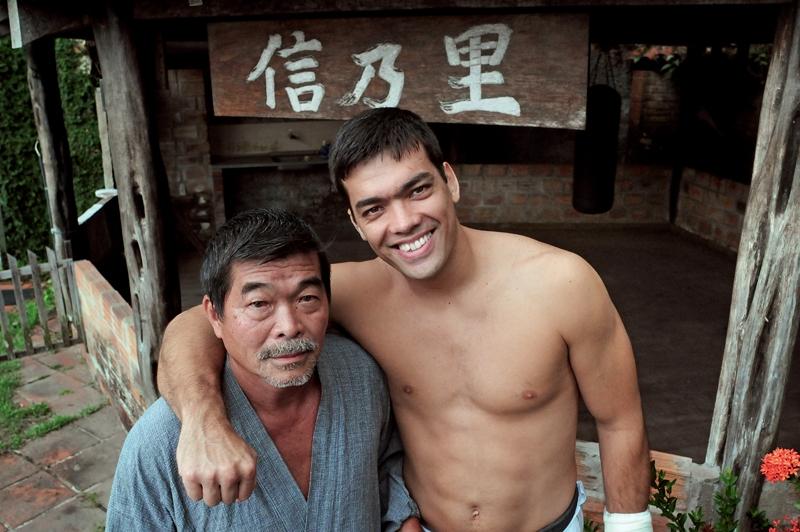 Yoshizo e Lyoto no quintal da casa do pai sob a placa Shin Sato (nome dos avôs do lutador, que batizaram um sítio que Yoshizo teve no Pará)
