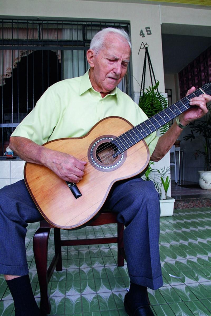Ernesto com o violão, em casa