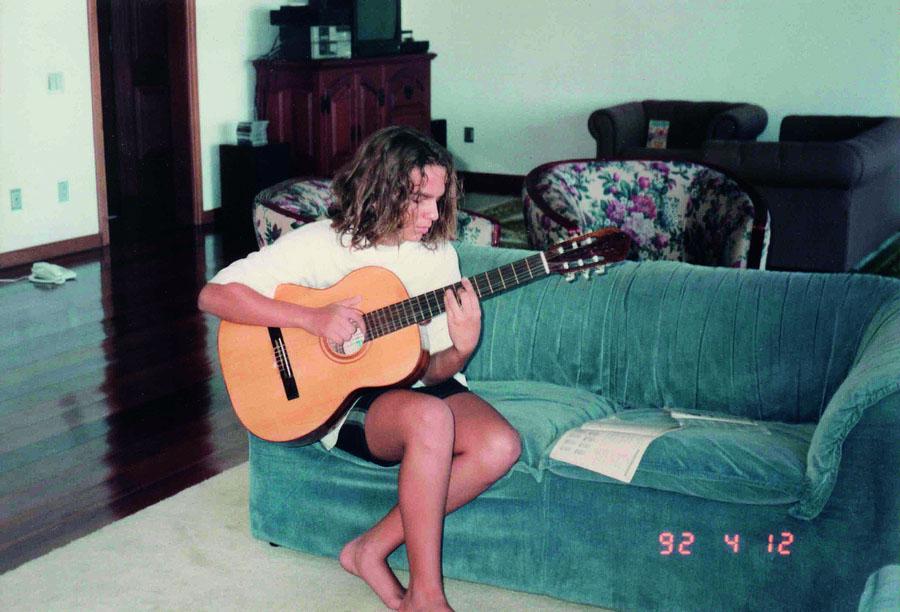 Estuda violão na sala de casa
