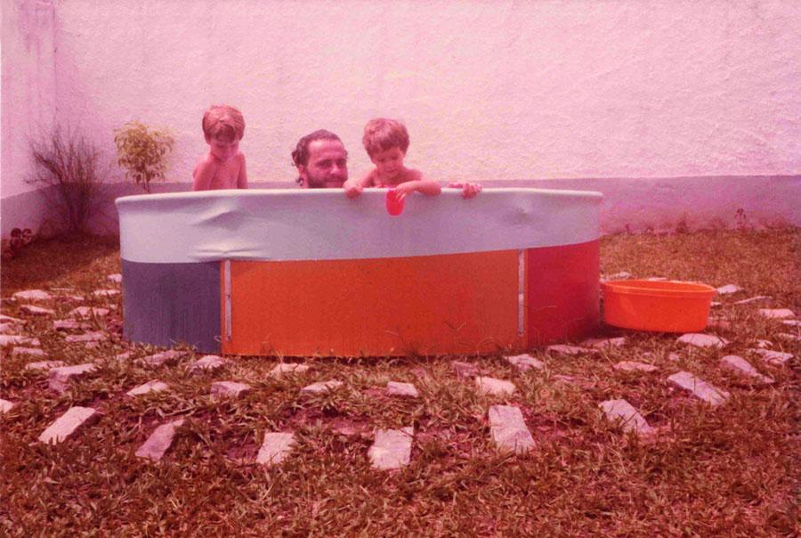 Com o pai e irmão na piscina de casa