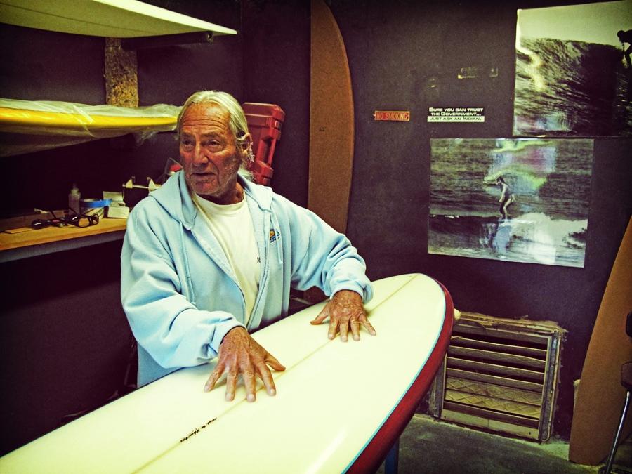 Johnny Rice em sua oficina de shapes em casa. No fundo, foto de sua mulher surfando em outros tempos