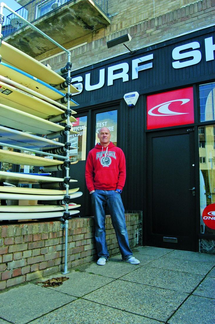 Shaun Taylor em sua surf shop, que ele abriu ao ouvir os rumores sobre o recife artificial