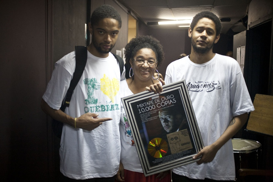 """Evandro, Jacira e Leandro seguram a placa que eles mesmos fizeram e se autoconcederam comemorando a """"mixtape de ouro"""" por 10 mil cópias vendidas"""
