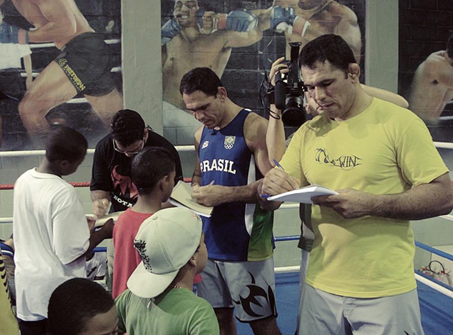 Dando autógrafos para crianças do projeto dos irmãos Nogueira, também no Rio, ao lado de Rogério Minotouro