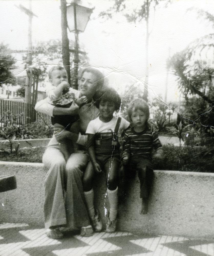 bebê com a mãe, a irmã mais velha e um vizinho