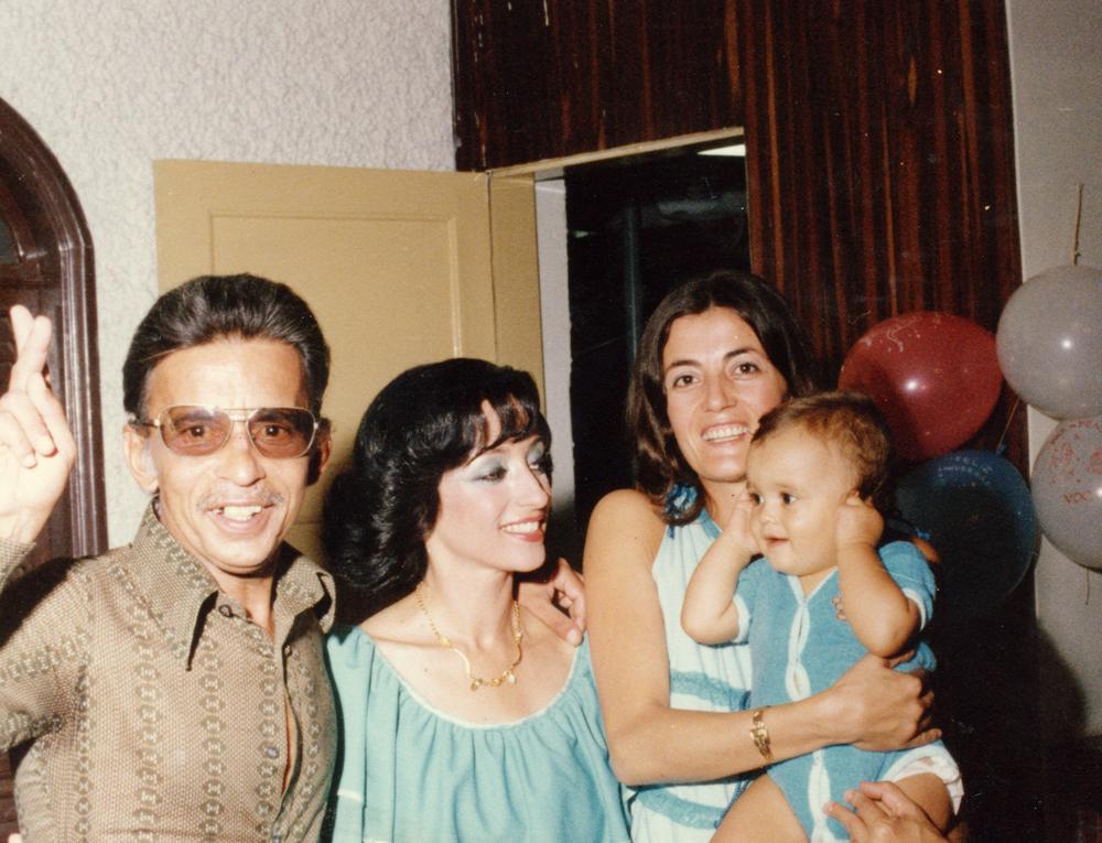 Mauricio de macacão azul no colo da mãe e ao lado do pai, de óculos