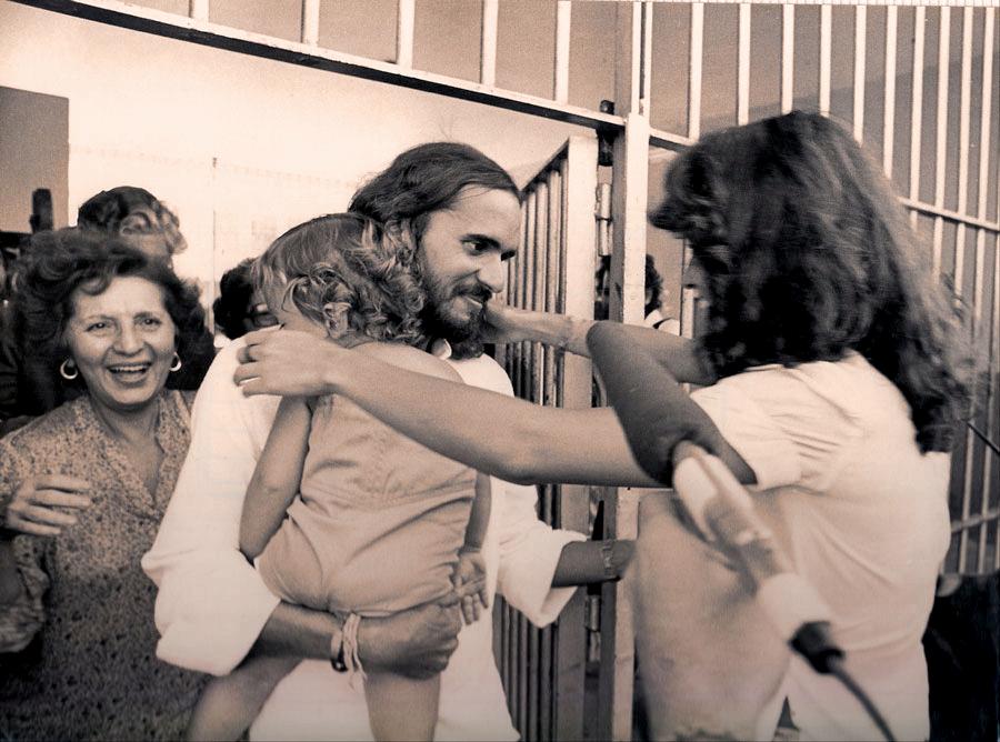 Com o filho nos braços, reencontrando a esposa e a mãe (sorrindo atrás dele) após ser libertado