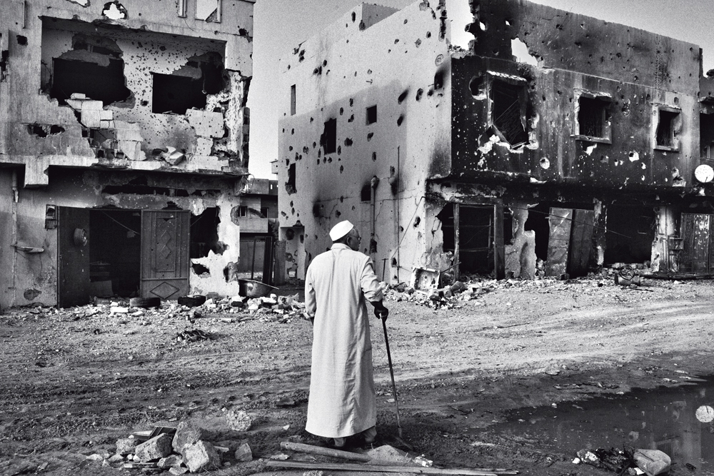 Morador observa a destruição da guerra em mais uma imagem de Maurício Lima feita para o New York Times na cidade síria de Sirte ano passado