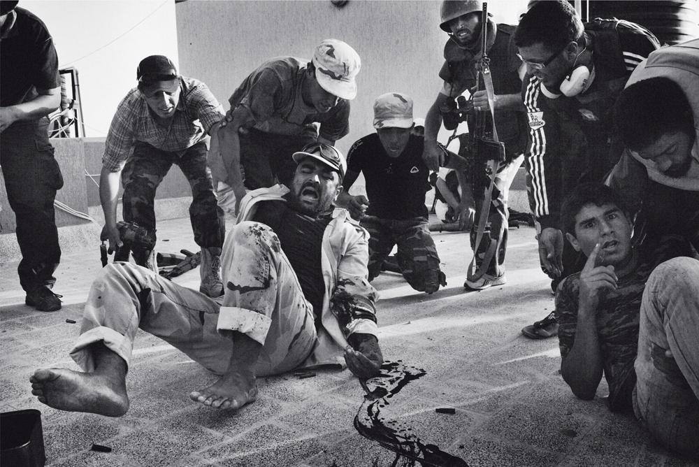 Rebelde sírio que lutava contra as forças do ditador Gaddafi tomba baleado (no braço) logo após outro tiro ter atingido o peito do homem caído no canto direito da imagem. O flagrante de Maurício Lima foi captado ano passado em uma cobertura da cidade de Sirte