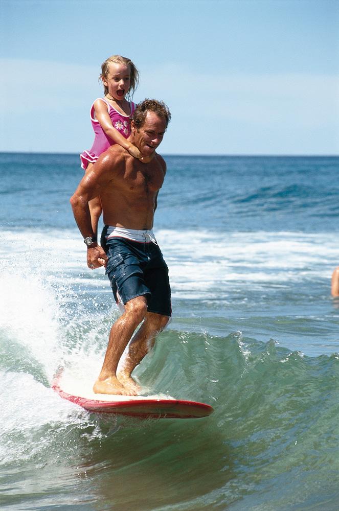 Tom com a filha Jenna nos ombros, surfando em Newport, em 2001