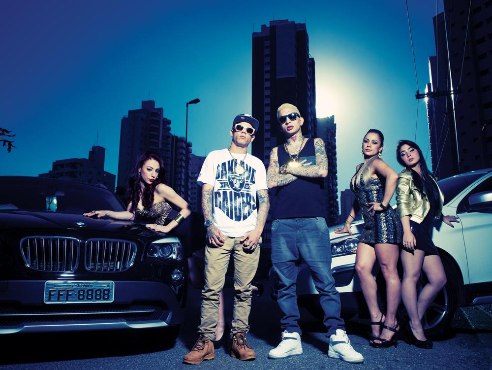 Mc Lon e Mc Guimê posam com os elementos básicos de seus videoclipes: carros, mulheres e acessórios de ouro