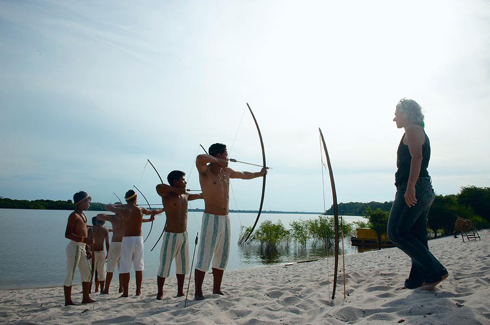 Os índios cambeba treinam na areia sob o olhar de Márcia Lot