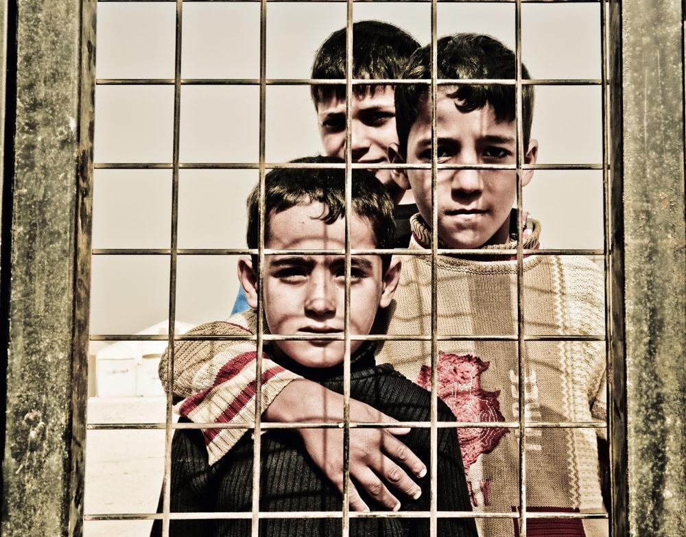 Meninos à espera da triagem do campo de refugiados de Al Zaatari