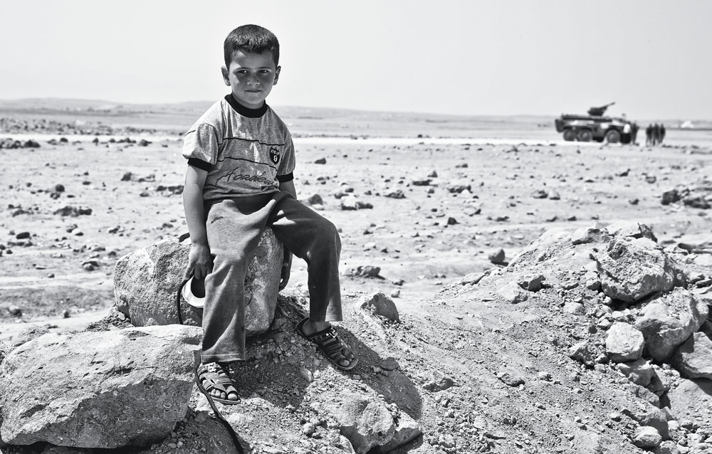 Criança com um tanque de bateria antiaérea ao fundo
