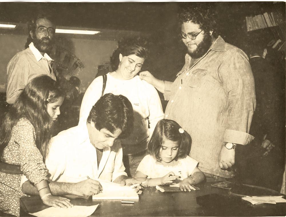 Nelson autografando seu primeiro livro Música humana música, em 1978, entre as filhas Joana e Esperança