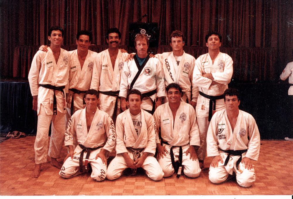 foto de Rorion Gracie com o aluno Chuck Norris (de pé), Rickson  Gracie (ajoelhado) e alguns praticantes célebres do jiu-jítsu em seus primórdios
