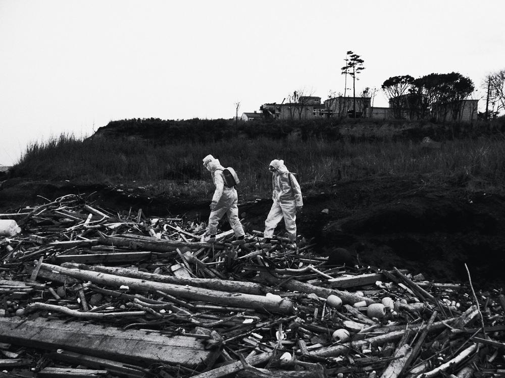 A dupla de artistas indonésios Tita Salina e Irwan Ahmett, caminhando pelos destroços varridos pelo tsunami na praia