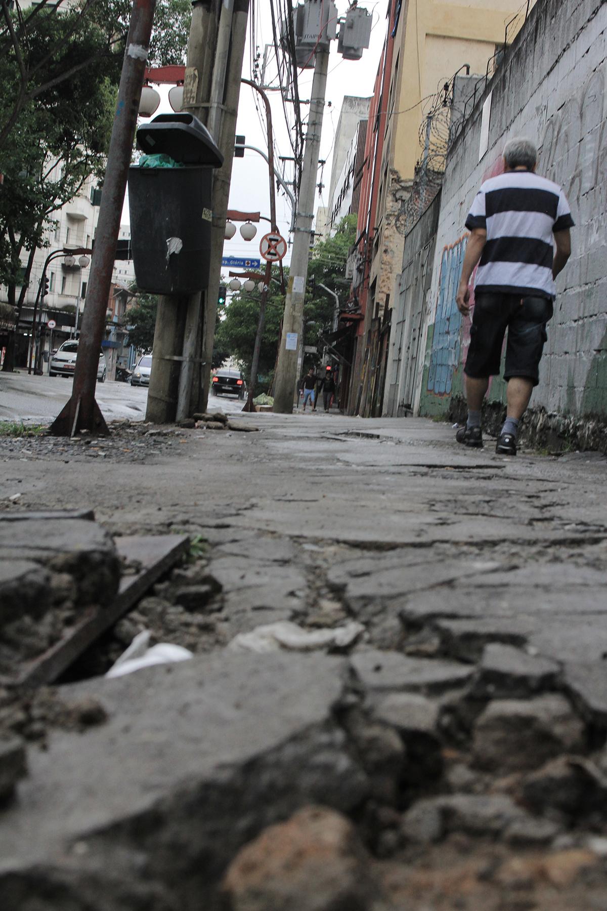 Rua Barão de Iguape, perto do nº 222, Liberdade: o que era um caminho de pedestres parece ser engolido pelo bueiro. Ainda assim, há quem ande