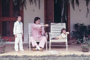 Aprendendo arco e flecha com o avô e o irmão, de pijama, no sítio Poço Fundo, em 1979