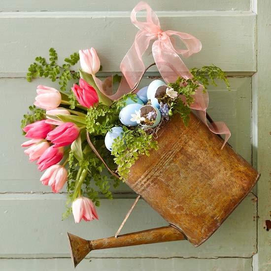 Um regador cheio de flores vira guirlanda de porta com a ajuda de uma fita de decoração