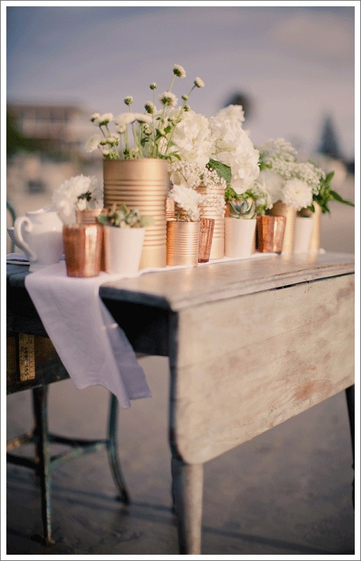 Copos e latinhas de tamanhos variados pintados por tinta spray dourada viram lindos vasinhos