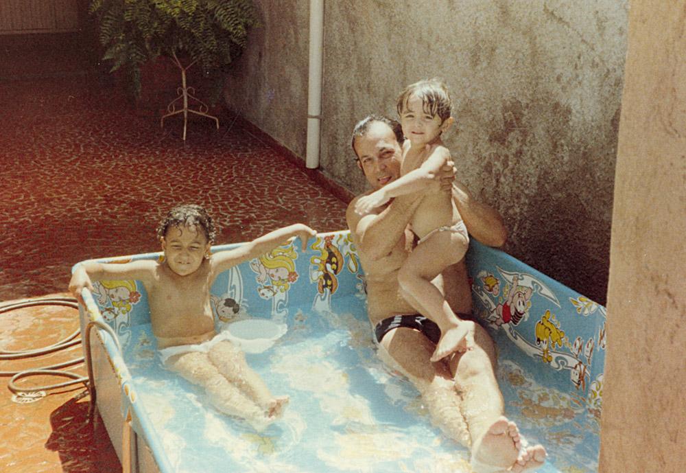 Aos 4 anos, no colo do pai, Joaquim, com a irmã, Aline, se refrescando na piscina da Turma da Mônica, no quintal da casa onde cresceu