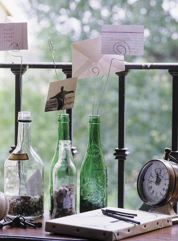 """As garrafas também podem virar porta recados bem originais. Ponha pedrinhas dentro delas para """"segurar"""" os arames, que devem ser enrolados na ponta, formando o espiral que vai prender os bilhetinhos ou fotografias"""