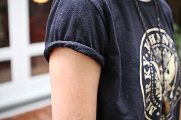 Como a camiseta é larga, as manguinhas dobradas ajudam a disfarçar