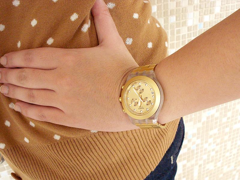 Detalhe no relógio dourado da Swatch que se encaixa bem com as cores frias do look.