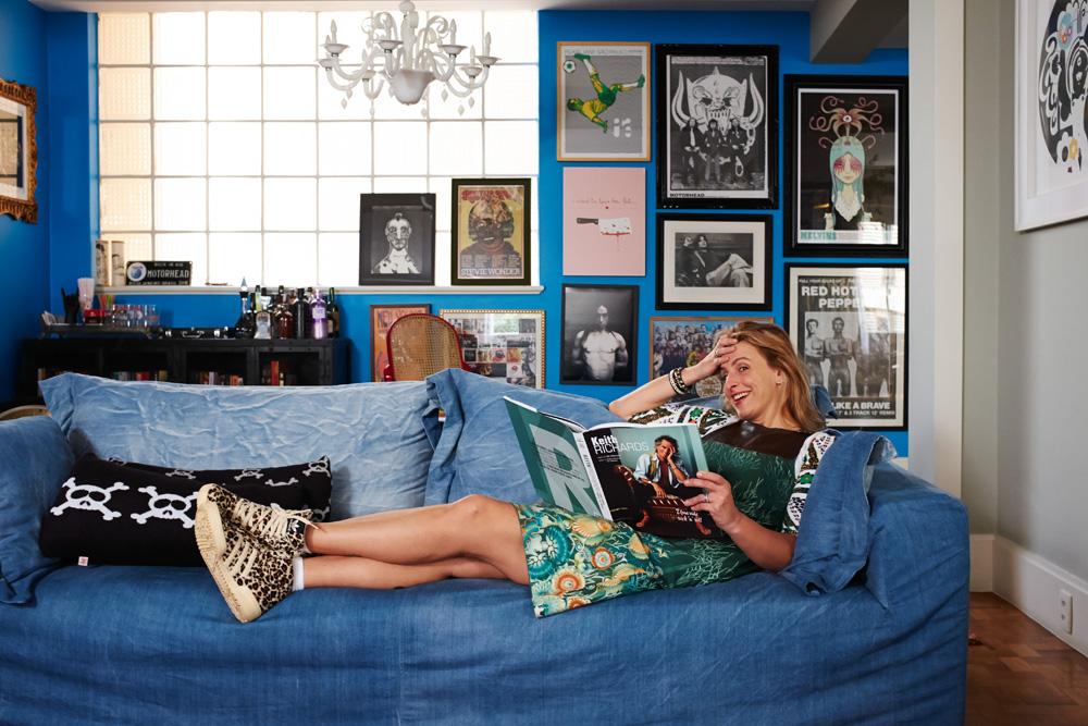 Tudo Azul: Chris na sala de estar, em meio à coleção de pôsteres de música, um minibar e o livro de Keith Richards, um de seus ídolos
