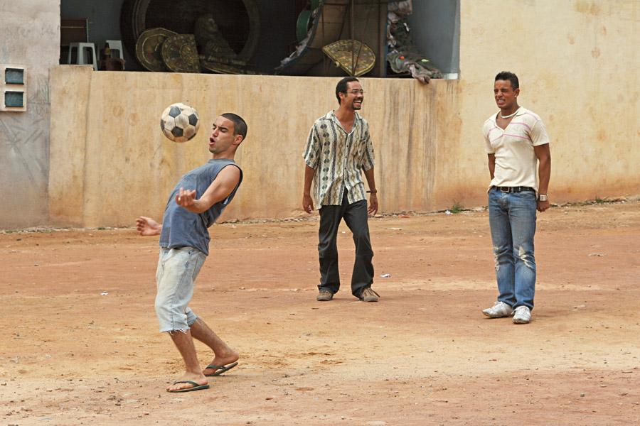 Trio de amigos no campo de futebol do bairro