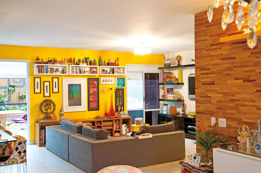 Casa cheia: O sofá da Micasa tem apoio reforçado para poder acomodar vários amigos. Ao fundo, a tal parede amarela que a designer tanto queria