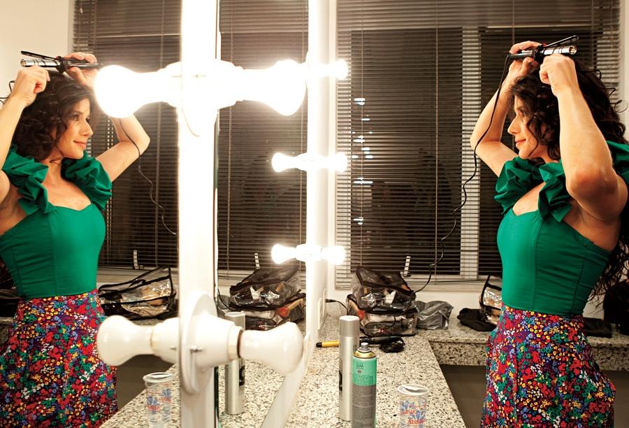 Paula e seu baby liss. É ela quem faz os cachos, a maquiagem e as unhas antes dos shows