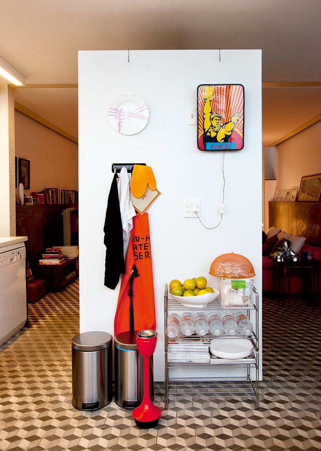 Soltos l A parede branca revestida de fórmica não chega ao teto nem encosta em parede alguma. Mas é ela que faz a divisória entre a sala de TV e a cozinha. O prato pendurado foi um presente e o cinzeiro de piso vintage laranja veio de Marselha