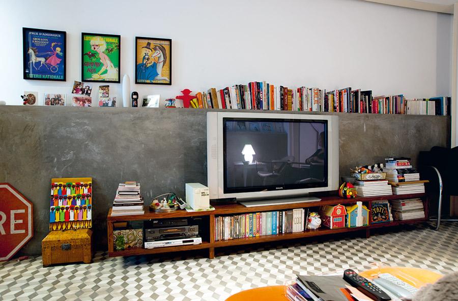 Concreto l A meia parede de concreto impermeabilizado foi uma maneira de garantir que o subsolo não tivesse infiltrações nem ficasse úmido, e acabou virando uma bancada para livros e objetos. Os quadrinhos vintage da loteria francesa foram comprados em Marselha