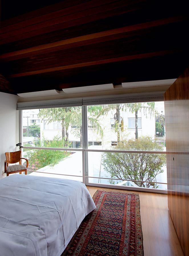 Três andares l No quarto, a esquadria de alumínio e vidro, presente nos três andares, é o diferencial da casa. A passadeira persa e a cadeira Biedermeier vieram da casa da mãe