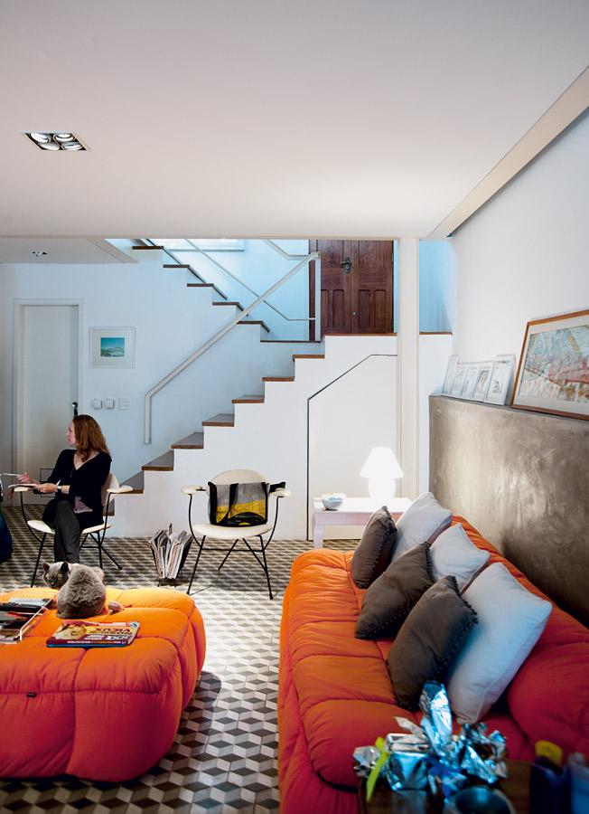 Cantinho l O sofá laranja Strip é da Forma. A luminária é da Lumini. Na parede de concreto, fotos de Damien (www.dmsphoto.com) e quadrinho da infância de Tatiana