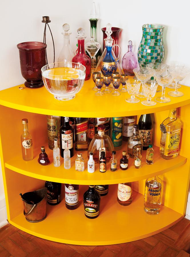 Vai uma bebidinha? l O bar de laca amarela, também feito pelo marceneiro Adelmo, armazena as bebidas, a coleção de garrafas e vasos e o peixinho de Manuela